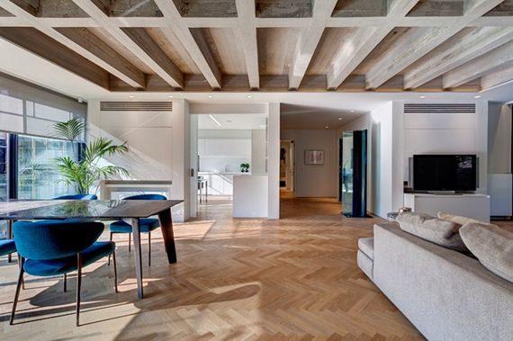 Salas integradas com vigas aparentes e um incrível piso de tacos de madeira.