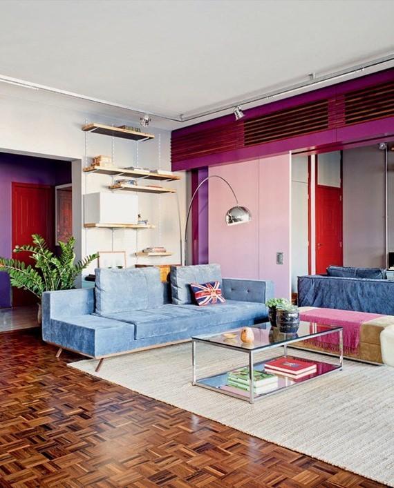 sala de estar com sofa cinza, tapete claro e acessorios modernos que contrastam com o piso de tacos de madeira