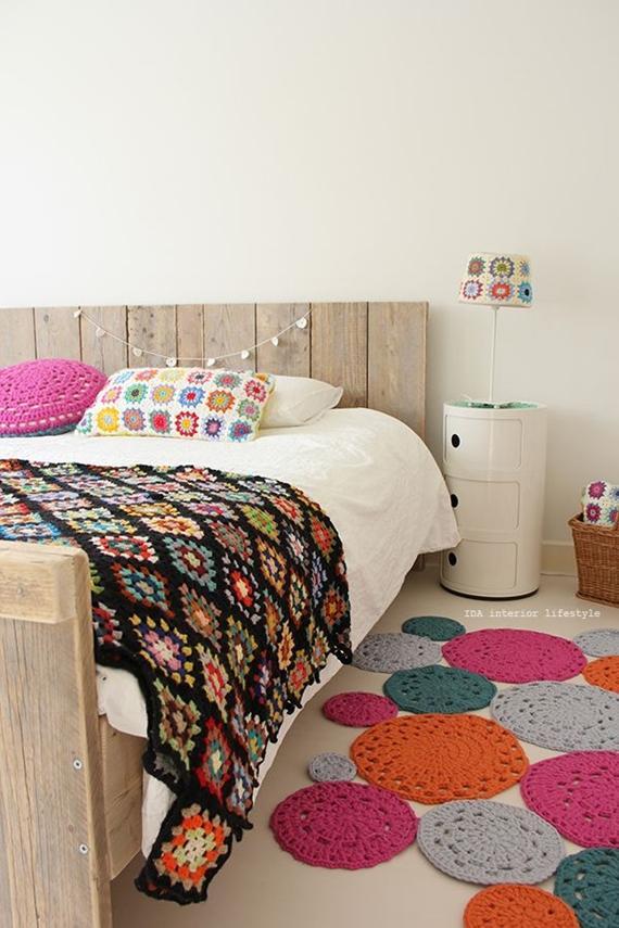 quarto de casal decorado com almofadas, colcha, tapete e abajur de crochê