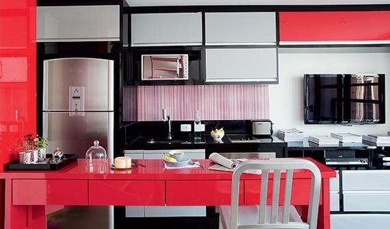Cozinha integrada com detalhes em vermelho.