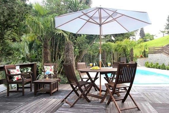 Deck de madeira decorado com bancos, mesa com cadeiras e um incrível ombrelone