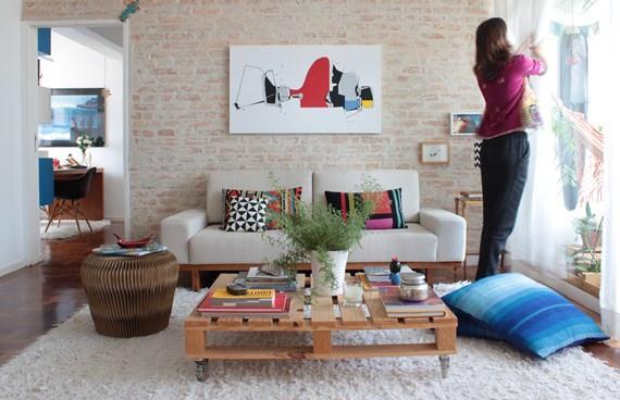 Sala de estar com mesa de centro feita de pallet e parede de tijolinho aparente